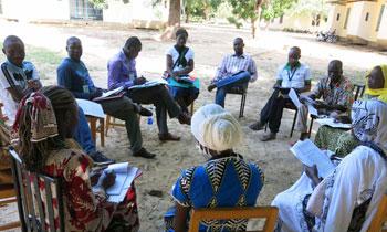 Les gens s'assoient dans un cercle de chaises et discutent