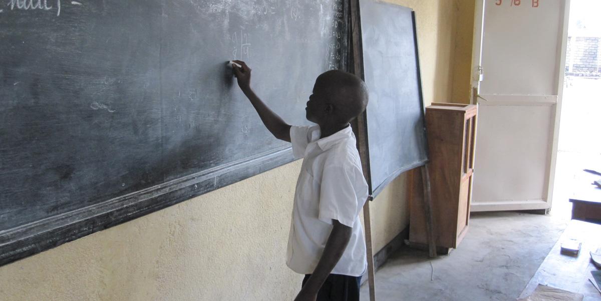 Child writes on the school blackboard