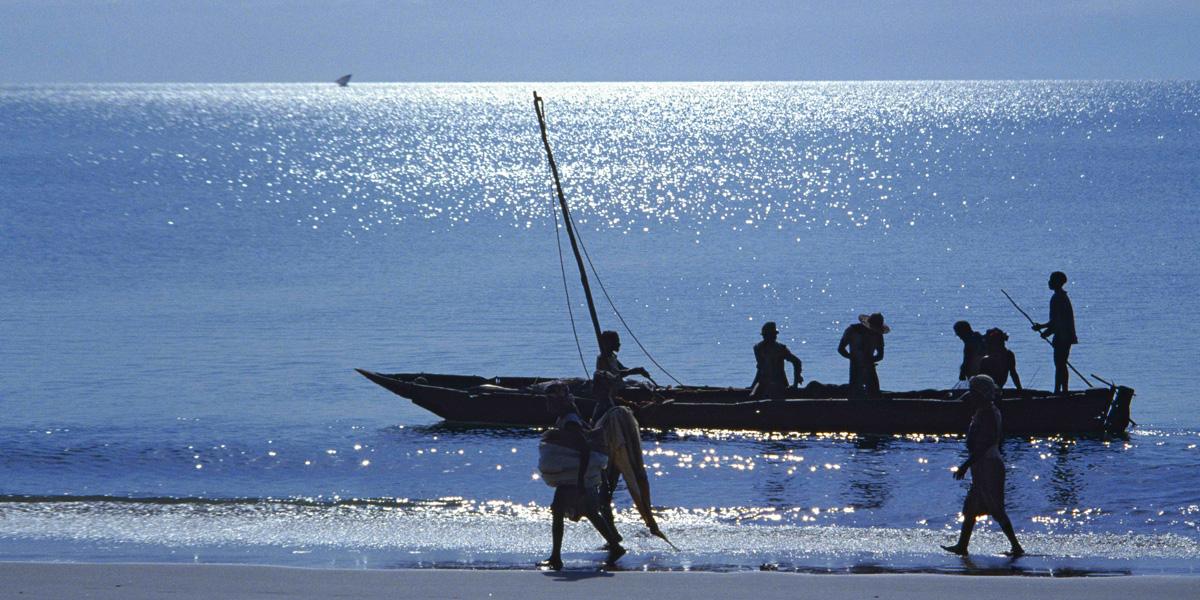 Plage avec un bateau de pêche et personnes